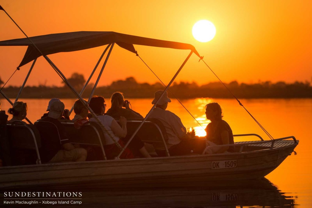 Xobega Island guests admire the sunset from their boat in the Okavango Delta