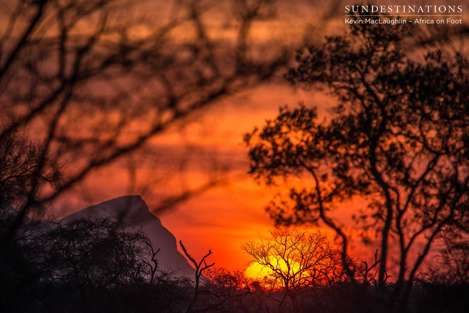 A peak of the Drakensberg Mountains peeks over the horizon as the setting sun bathes the sky in bright colours of summer